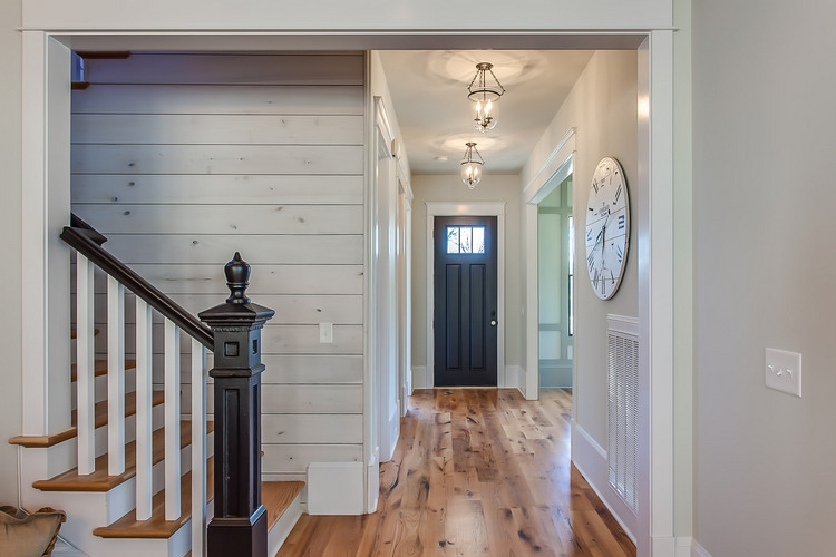 white hallway with whitewashed wood and black door