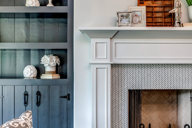 blue bookcase with white walls and white fireplace