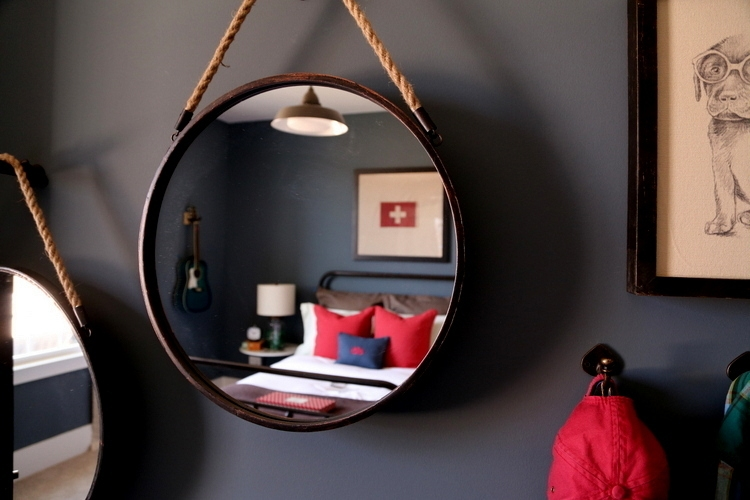 boys bedroom with dark walls and red accents with a mirror