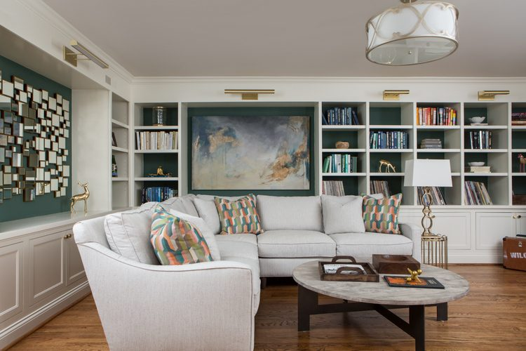 white sectional sofa with white walls and built-in bookcases with green backs of bookcases and coral accents with gold art lighting