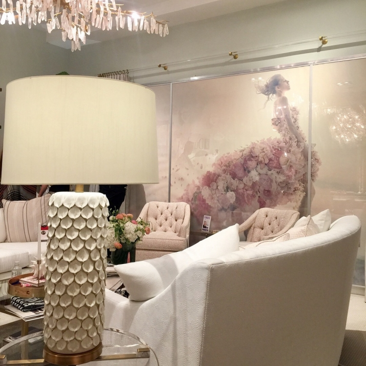 Crypton fabric for Duralee at High Point Furniture Market blush pink and white showroom with white shell lamp, pink tufted chairs, white sofa, and art with dress made of pink flowers