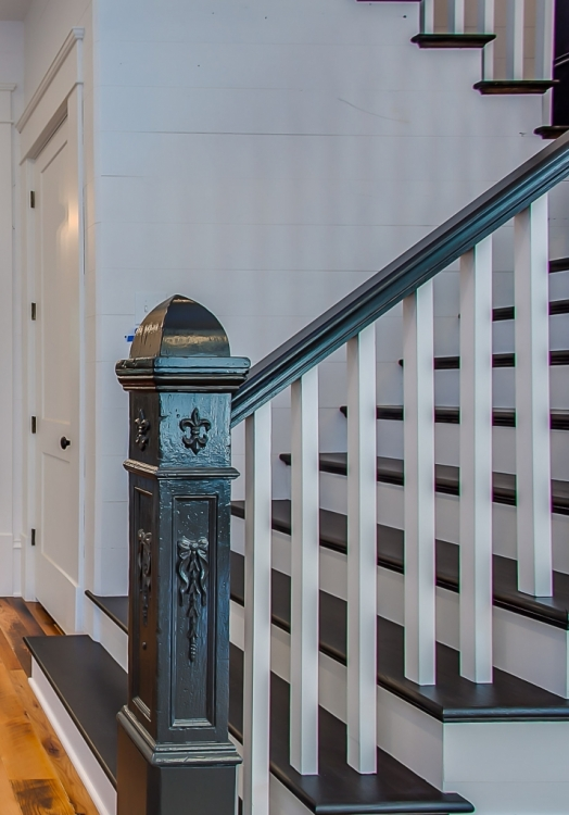 antique staircase newel post and handrail painted black with white shiplap