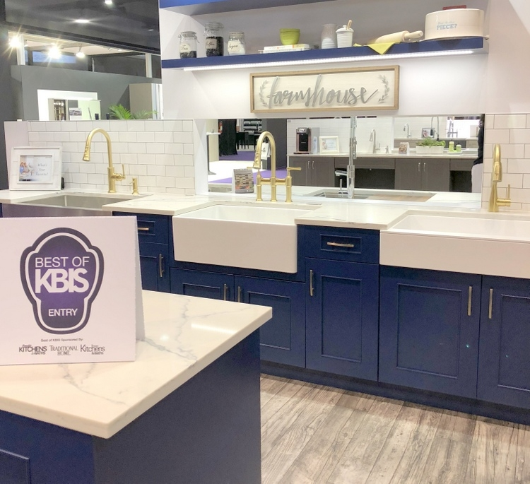 farmhouse style kitchen at 2018 KBIS with navy blue kitchen cabinets and gold faucets