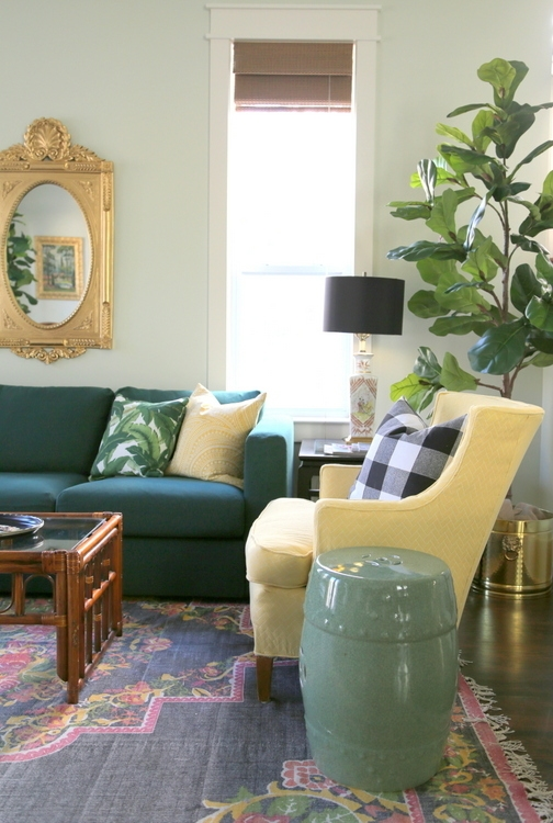 beach house design with dark green sofa, black rug, yellow chairs, Benjamin Moore Silken Pine on walls and fiddle fig leaf tree