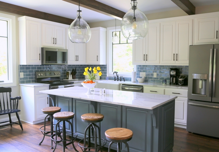 modern farmhouse white kitchen cabinets with dark blue island and blue subway tile and cambria brittanica countertops and industrial bar stools