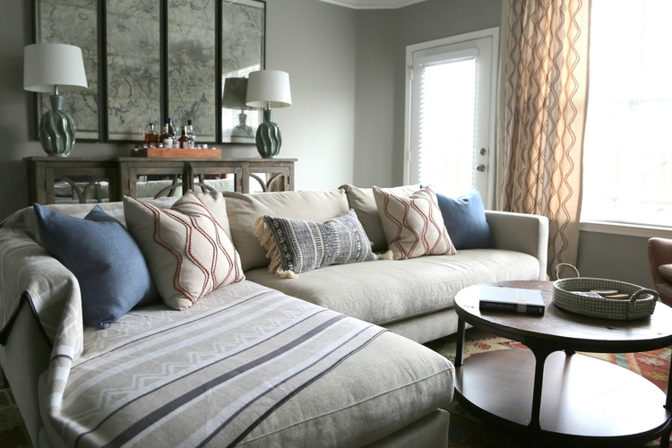 masculine room design by The Decorologist with Pottery Barn sectional chaise sofa, round rustic wood coffee table