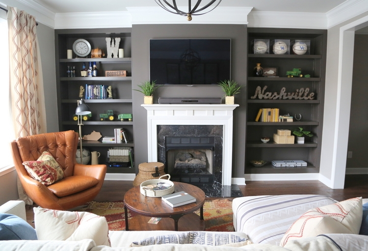 dark gray bookcases with midcentury leather swivel chair Nashville design by The Decorologist