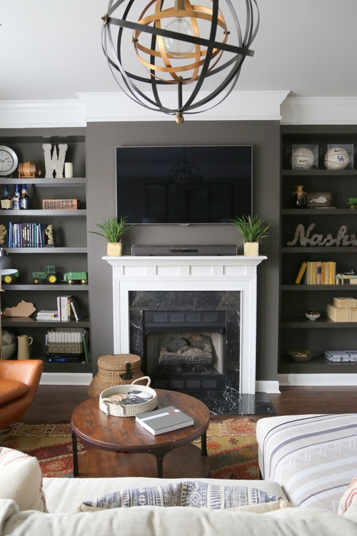 dark painted bookcase and fireplace with white mantel