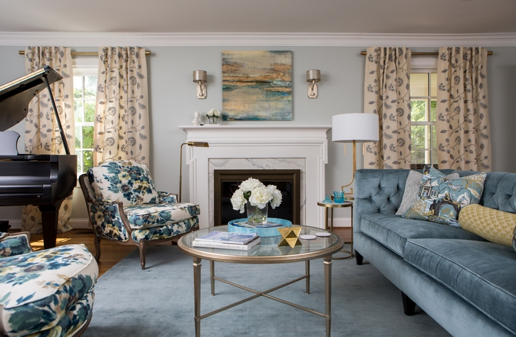 light blue living room walls with blue velvet sofa and round coffee table and pair of blue floral chairs design by Kristie Barnett, The Decorologist