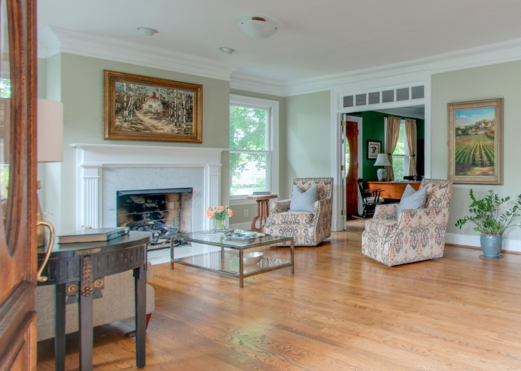 staged historic living room white white millwork fireplace and light gray green walls