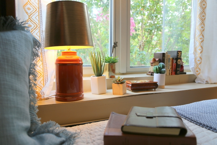 window ledge in dorm room with vintage orange lamp and succulents
