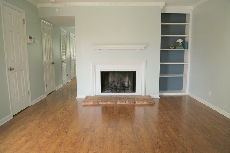 light gray blue walls in rental property with fireplace and built in bookcases