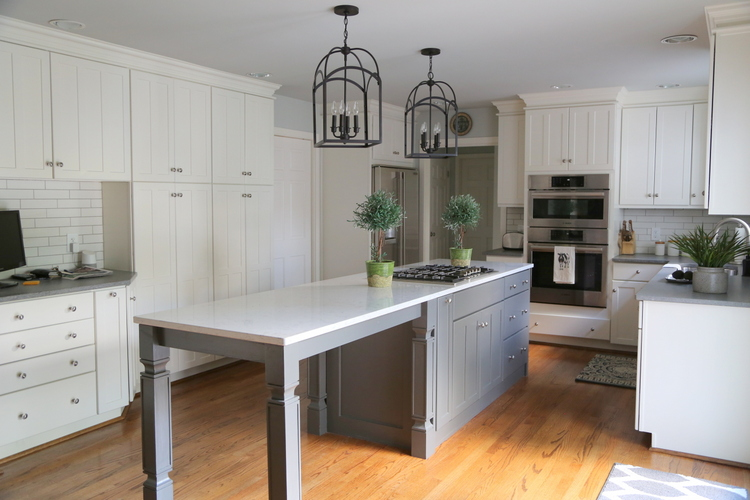 white kitchen cabinets with long quartz island and iron lantern light fixtures by Kristie Barnett, The Decorologist