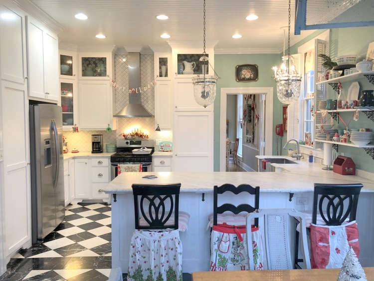 turquoise kitchen with marble countertops and marble floors and mismatched counter stools with vintage aprons