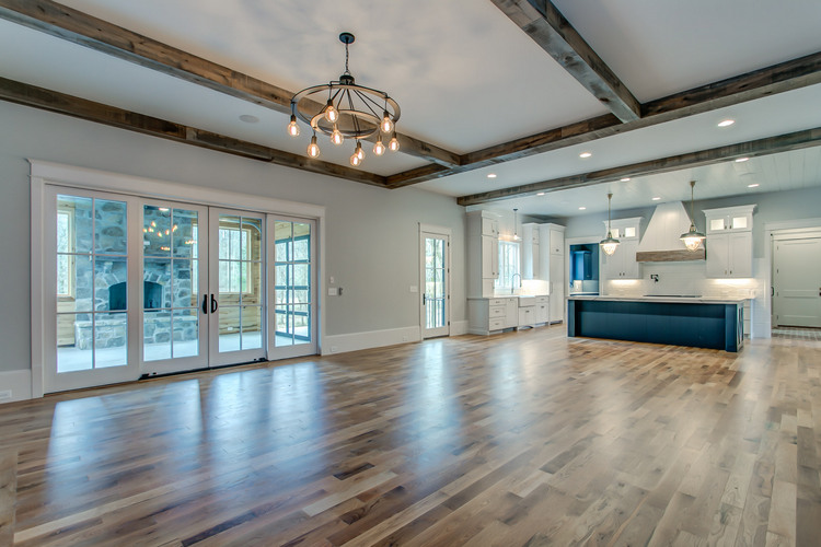 open floor plan home with dark wood beams on ceiling