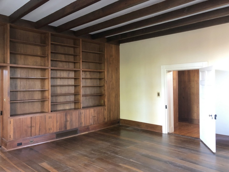 dark paneling library with wood stain beams