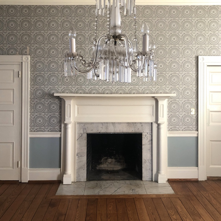 historic dining room fireplace mantel with crystal chandelier