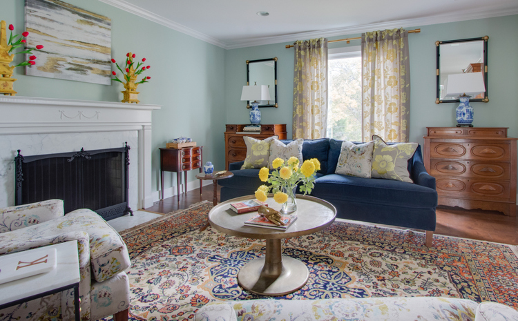 blue sofa in living room with antique rug and green walls